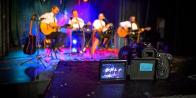 Na scenie SCK czterech muzyków z zespołu ALbo i Nie. Na pierwszym planie aparat fotograficzny.