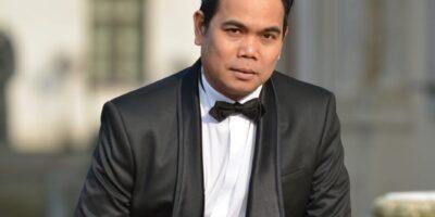 Wokalista - Alexander Martinez w czarnym czarniturze, z czarną muchą, na tle budynków