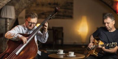 Na zdjęciu muzycy Bohdan Lizoń i Grzegorz Piętak siedzą przy stoliku w kawiarni i grają na instrumentach