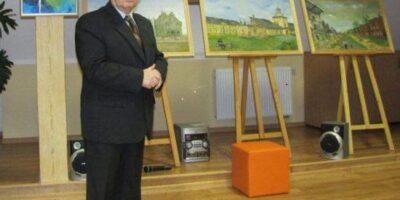 Andrzej Sodowski na tle czterech plac malarskich, znajdujących się na sztalugach.