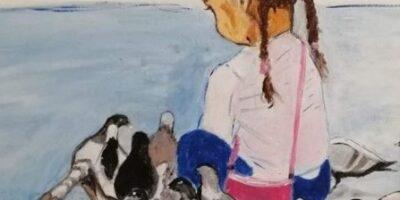Mała dziewczynka w dwóch warkoczach otoczona gołębiami.