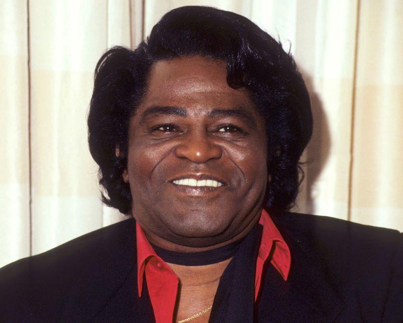 Ciemnoskóry mężczyzna w średnim wieku na tle kremowej ściany. Na twarzy widać uśmiech, jego włosy są średniej długości.