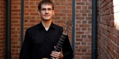 Młody mężczyzna w okularach ubrany w czarną koszulę. W lewej ręce trzyma gitarę klasyczną.