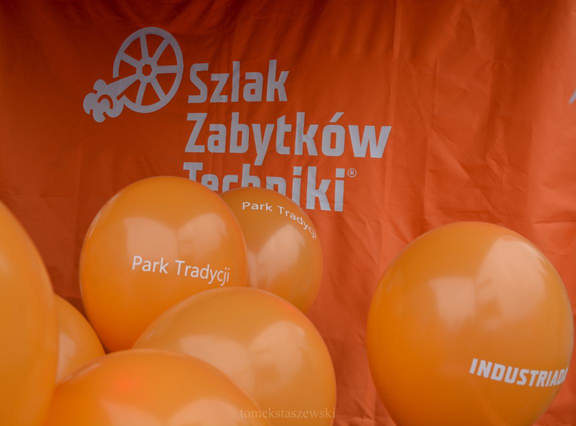Na pomrańczowym tle materiału z napisem Szlak Zabytków Techniki mamy pomrańczowe balony