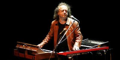 Józef Skrzek w brązowej skórzanej kurtce grający na instrumentach klawiszowych. Zdj. Archiwum SCK