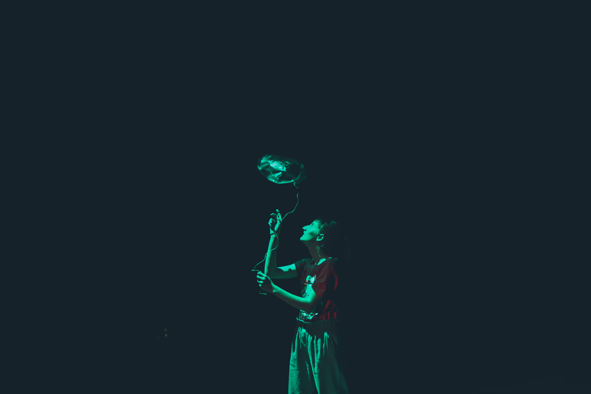 Młoda kobieta trzymająca w ręce balon. Jej wzrok skierowany jest na obiekt. Oświetlona zielonym światłem.