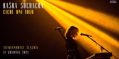 Na zdjęciu w żółtym świetle reflektora kobieta siedzi przy fortepianie i śpiewa do mikrofonu