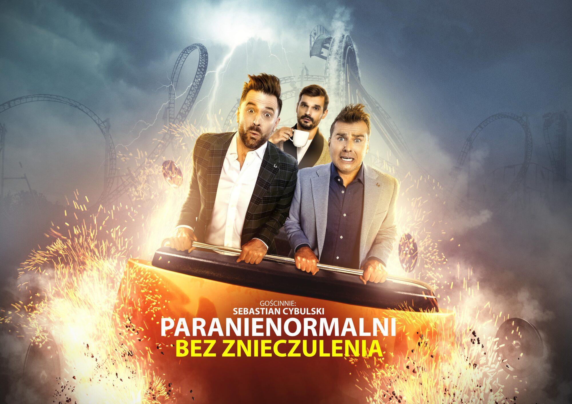 W wagoniku rollercoastera stoją trzej mężczyźni. Dwaj mają przerażone miny, trzeci pije kawę z filiżanki