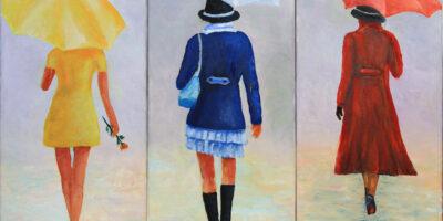 Trzy sylwetki kobiet: jedna ubrana na żółto, druga na niebiesko, a trzecie na czerwono. Wszystkie Panie trzymają parasol, który koreluje z kolorem ubrań