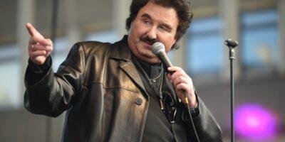 Mężczyzna w średnim wieku ubrany w czarną skórzaną kurtkę z uniesioną ręką do góry. W drugiej ręce trzyma mikrofon. Obok mężczyzna czarny statyw na mikrofon.