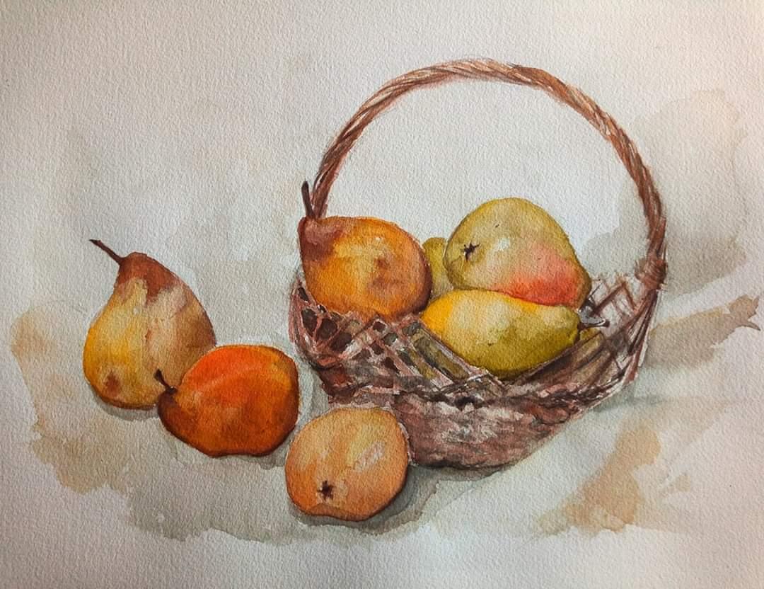 Wiklinowy brązowy koszyk z gruszkami oraz trzy gruszki leżące obok koszyka.