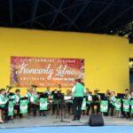 Na zdjęciu pełny skład Górniczej Orkiestry Dętej Bytom. Ubrani w biało zielone stroje muzycy grają na swoich instrumentach, na tle żółtej ściany amfiteatru. Foto Monika Bilska