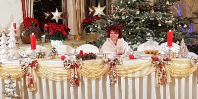 Piosenkarka Bernadeta Kowalska ubrana na biało, przy świątecznym, zastawionym stole na tle choinki.