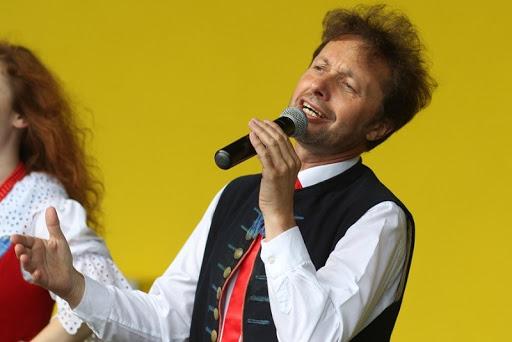 na żołtym tle ściany amfiteatru sylwetka Piotra Szefera w stroju ludowym, trzymającego w ręku mikrofon