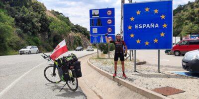 Tomasz Dzierga na granucy z Hiszpanią, obok tablicy granicznej. Obok stoi jego rower a na nim polska flaga.
