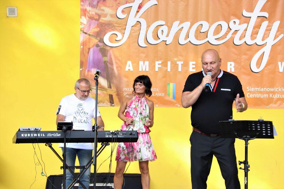 Widok na scenę, na któej znajdują się Piotr Herdzina i dwoje członków jego zespołu - wokalistka w biało-różowej sukience oraz klawiszowiec. Foto Monika Bilska