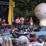 Widok ogólny na scenę i widownię amfiteatru podczas Pikniku Country. Na zdjęciu fragment widowni, scena z muzykami, balon reklamowy oraz motocykl będący dekoracją sceny. Foto Monika Bilska