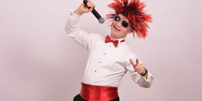 Wujek Kris czyli Krzysztof Kończyk ubrany w białą koszulę, czerwony pas i muszkę oraz w czerwonej peruce na głowie śpiewa do mikrofonu