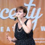 Zbliżenie na postać wokalistki Kai Karaplios, która ubrana w ciemną sukienkę śpiewa do mikrofonu trzymanego w dłoni. Foto Monika Bilska
