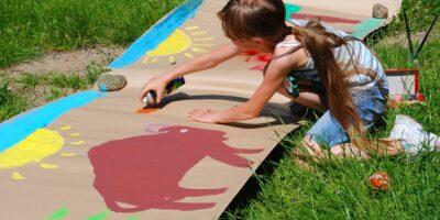 Dziewczynka malująca sprayem słońce, niebo i zwierzęta na dużym arkuszu szarego papieru.