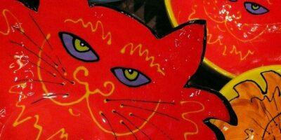 Zdjęcie przedstawia kolorowe naczynia ceramiczne z wizerunkami kotów.