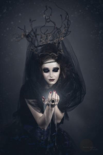 Zdjęcie przedstawia postać kobiety ucharakteryzowaną na czarownicę.