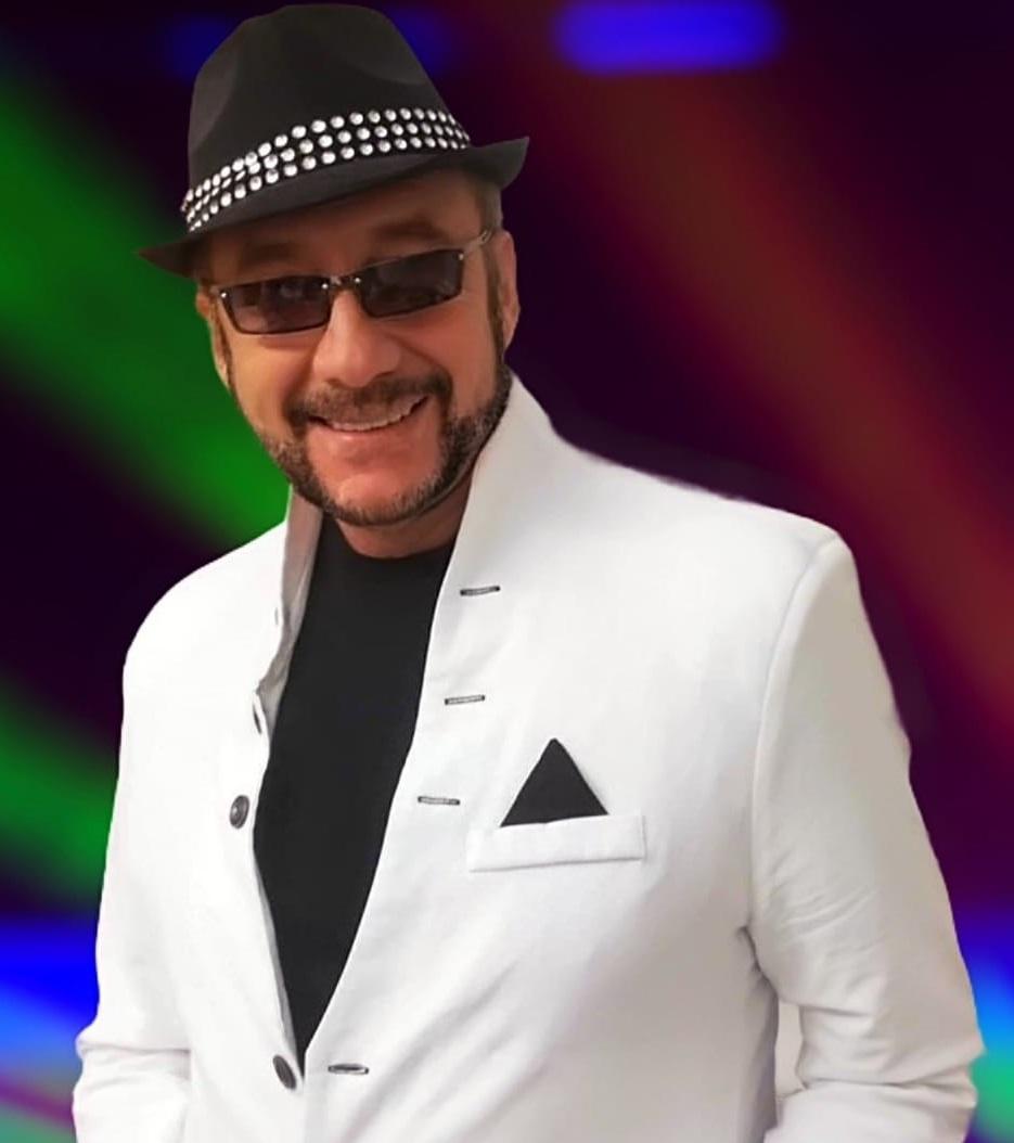 Mężczyzna w średnim wieku w białej marynarce, czarnej koszuli, czarnym kapeluszu z białą lamówką na tle kolorowych świateł.