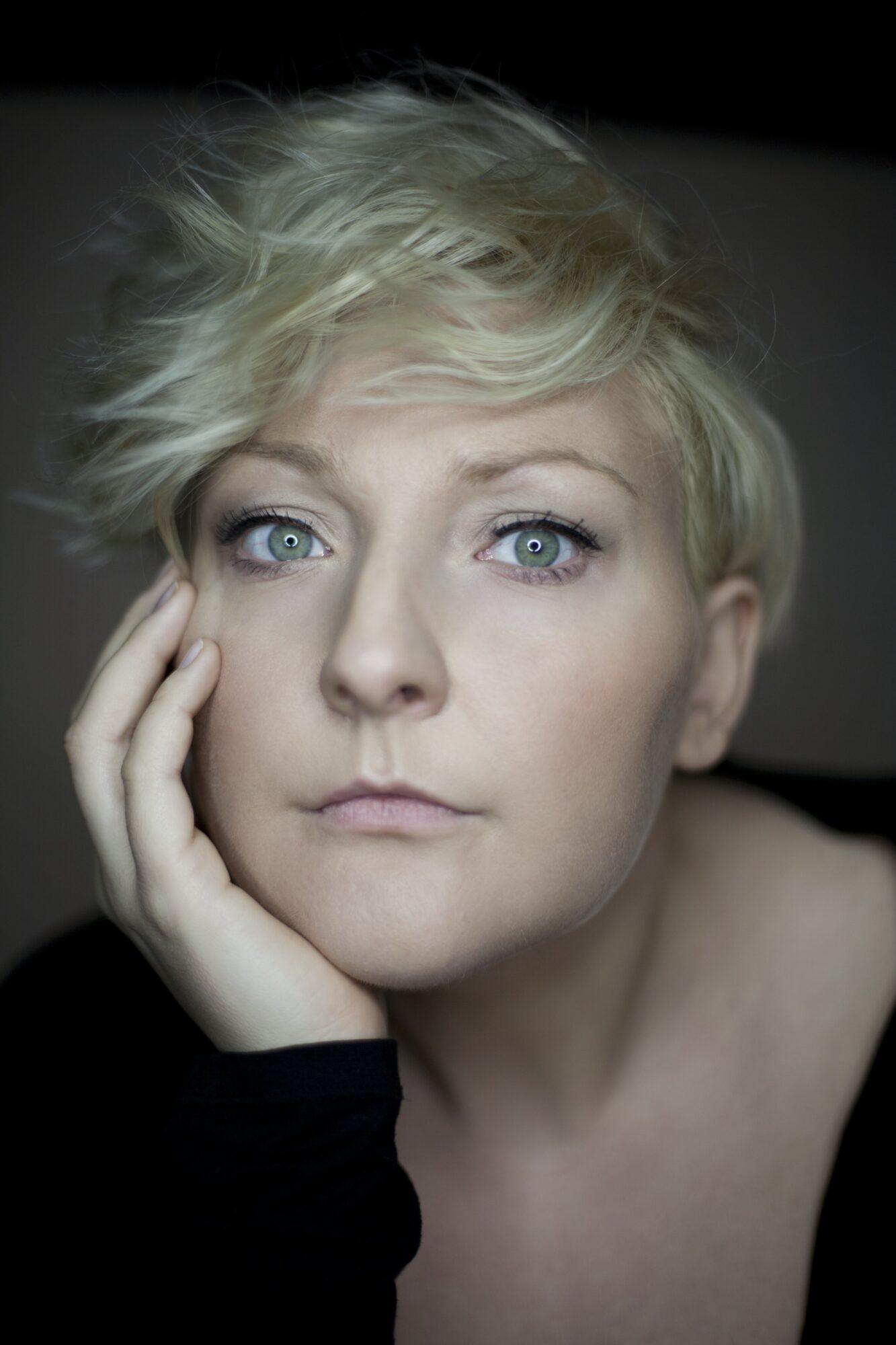 Kobieta, o krótkich włosach blond podpiera ręką podbródek.