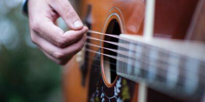 Zbliżenie na gitarę akustyczną oraz dłoń, grającą na niej