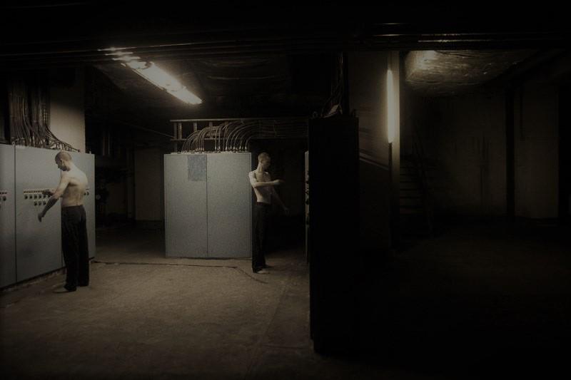 Dwóch mężczyzn w czarnych spodniach stojących w pomieszczeniu z metalowymi szafami