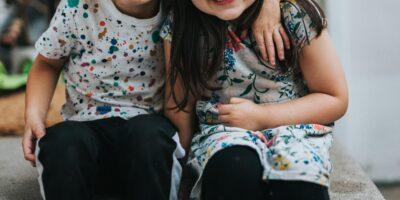 na zdjęciu dwie małe dziewczynki, objęte, uśmiechają się