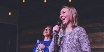 Dwie uśmiechnięte osoby trzymające w rękach mikrofony