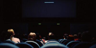 Ciemna sala kinowa z kilkorgiem uczestników . Widać kilka wolnych miejsc.