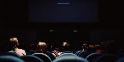 Ciemna sala kinowa pełna foteli oraz odwiedzających