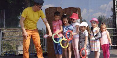 Na zdjęciu ubrany w kolorowy strój aktor bawi się z dziećmi, trzymającymi w rękach kolorowe kółka