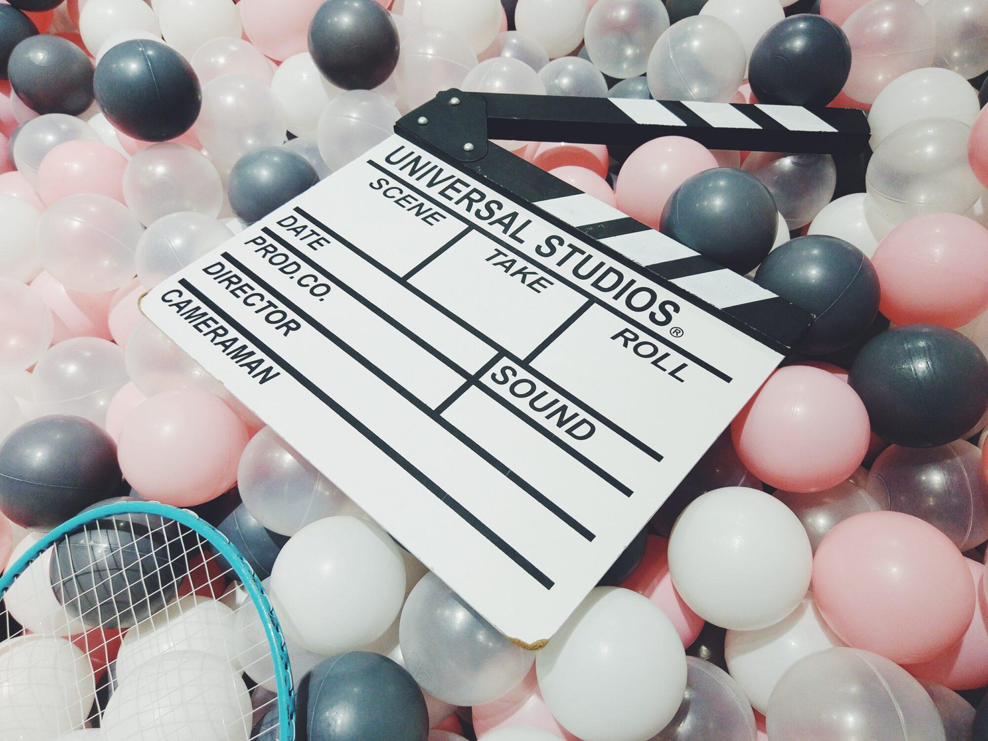 Czarno-biały klaps filmowy wśród kolorowych kulek.