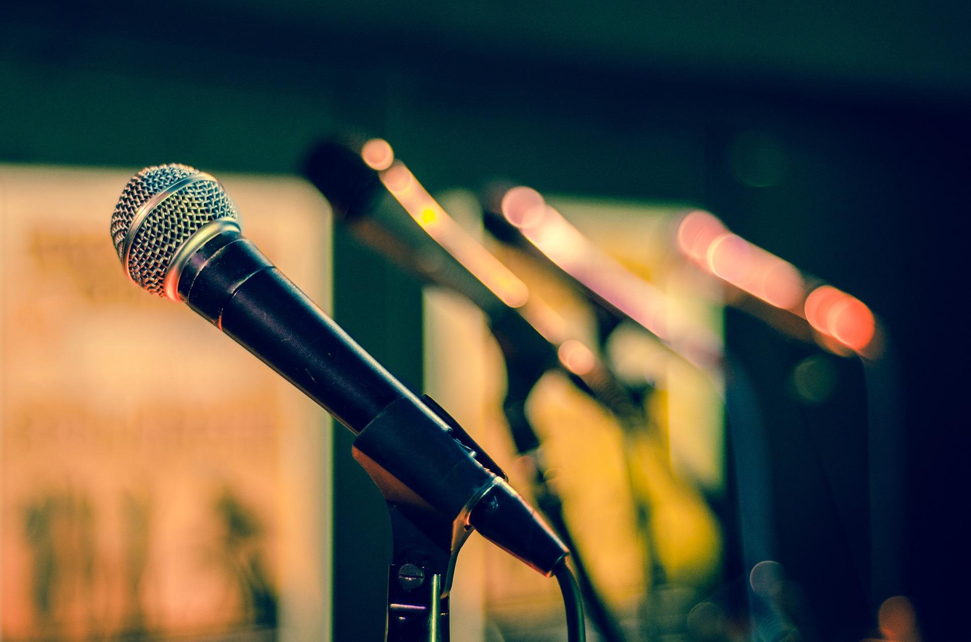 Na pierwszym planie mikrofon, na dalszym planie trzy dodatkowe mikrofony na statywach.