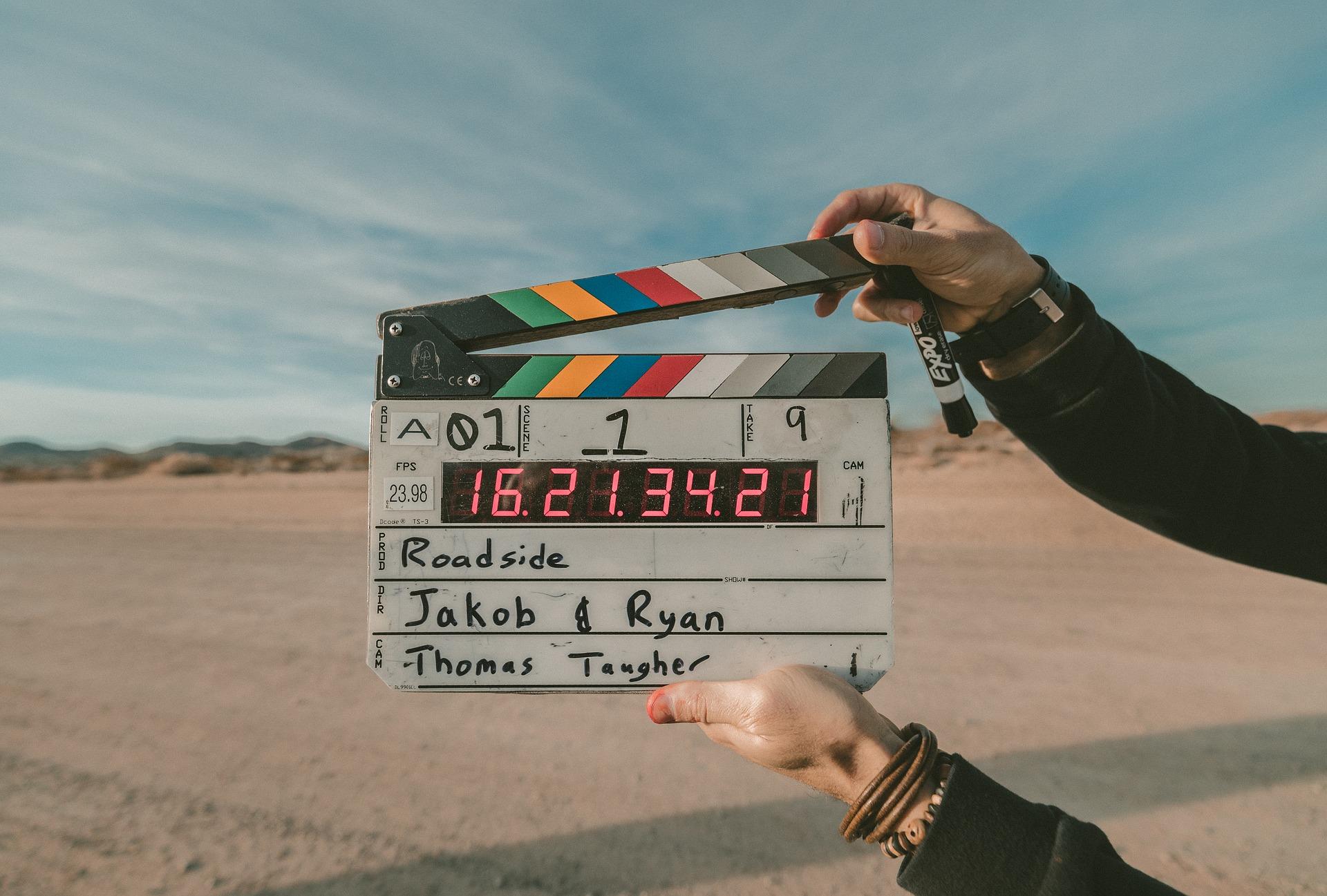 Klaps filmowy na tle piaszczystego podłoża.