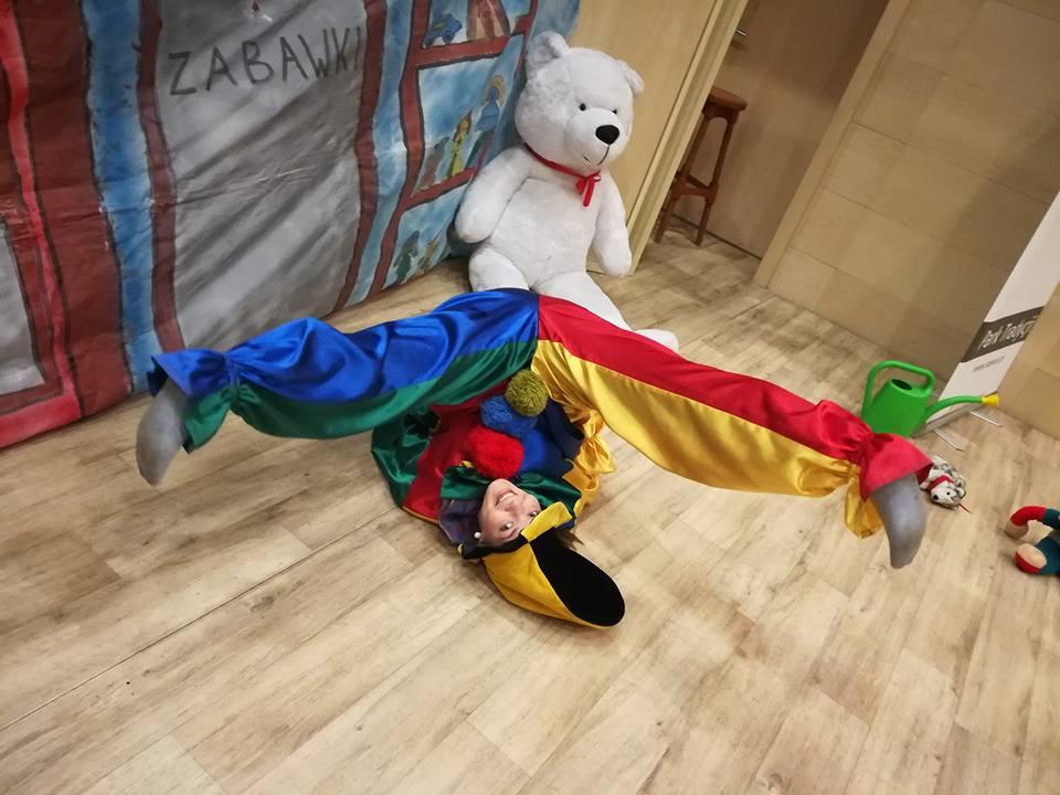 Kobieta przebrana za klauna, wygłupiająca się na podłodze