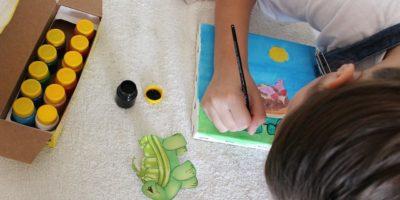Mała dziewczynka o brązowych włosach siedzi podparta na podłodze i maluje. Obok niej farby.