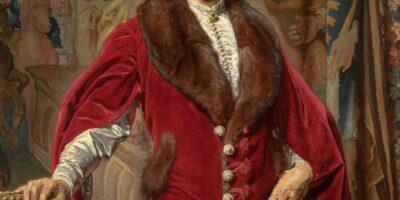 Zdjęcie przedstawia portret Józefa Ciechońskiego. Widzimy mężczyznę w stroju historycznym w kolorze czerwonym