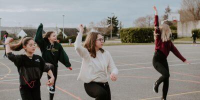 Na boisku szkolnym tańczy grupa młodych dziewcząt, ubranych w stroje sportowe