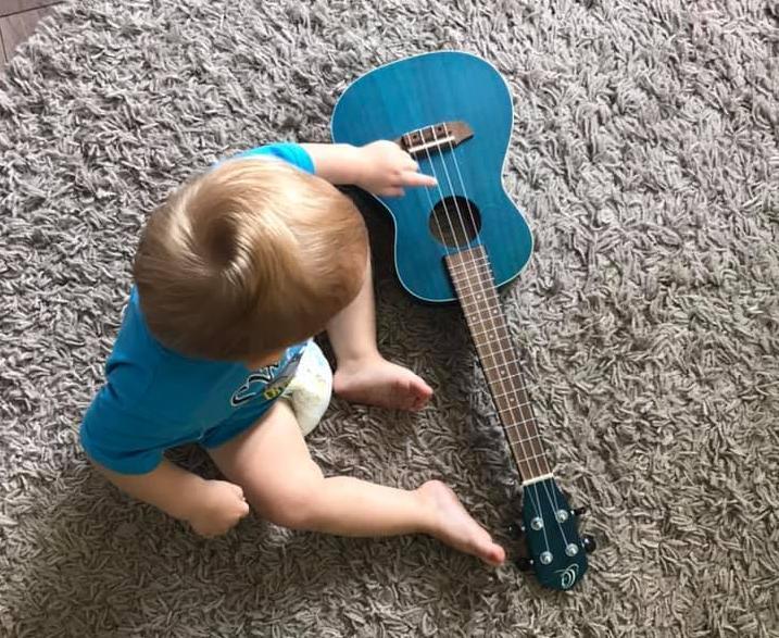widok z góry na małe, jasnowłose dziecko, siedzące na czarym dywanie i bawiące się niebieską gitarą