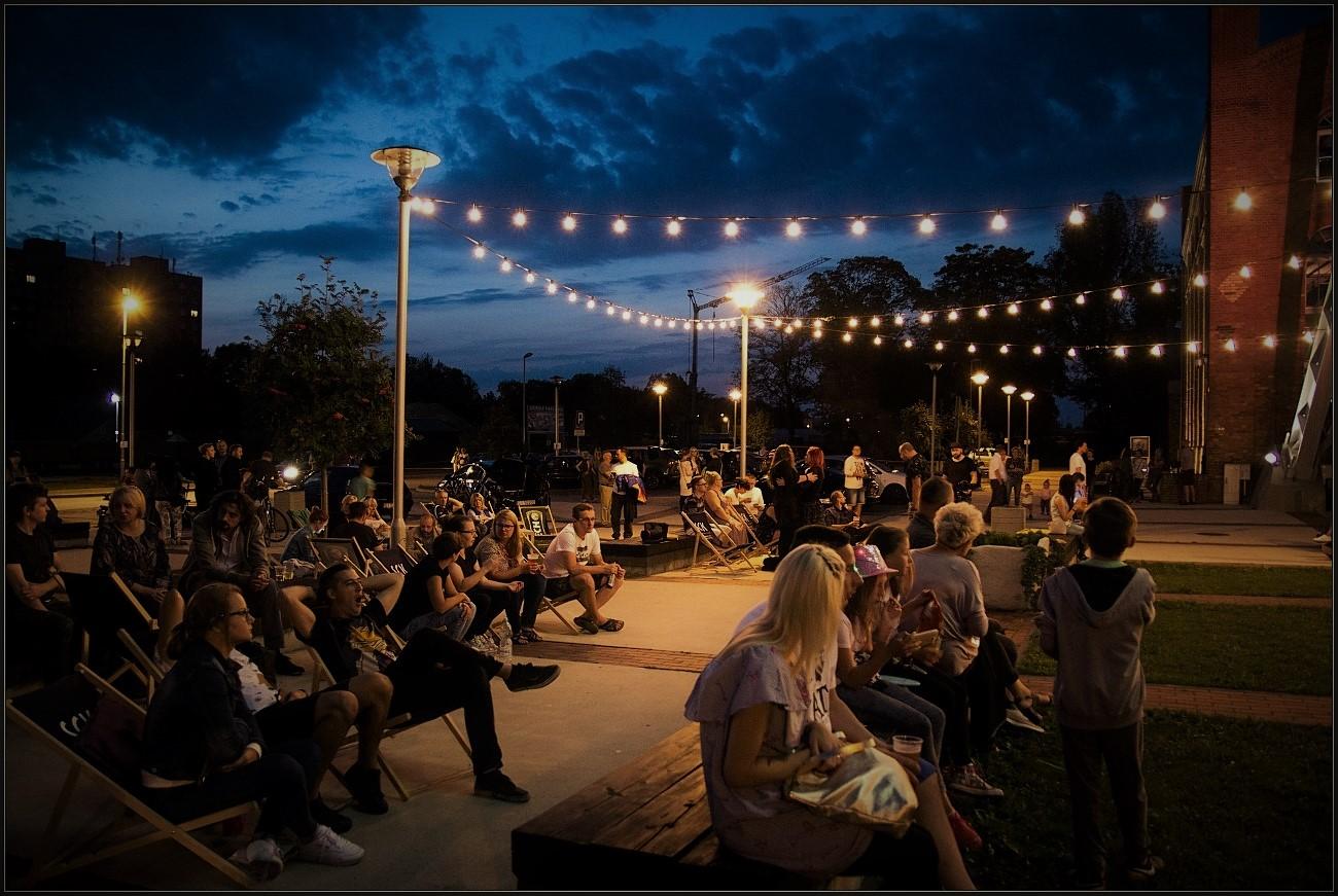 Wieczór, ludzie siedzący na ławkach przed budynkiem Parku Tradycji w Siemianowicach Śląskich