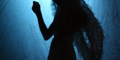 Ciemna, mroczna postać na tle płótna podświetlonego niebieskim światłem.